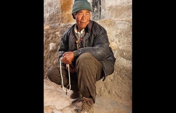 hombre recitando mantras con el yapa mala en la mano