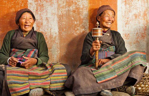 mujeres Sherpa recitando mantras con la rueda de oración
